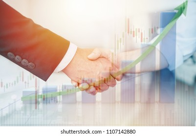 Double exposure handshake of two businessmen with growth chart on background