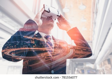 The double exposure image of the business man using a VR glasses during sunrise overlay with cityscape image. the concept of communication, gaming, internet of things and future life.