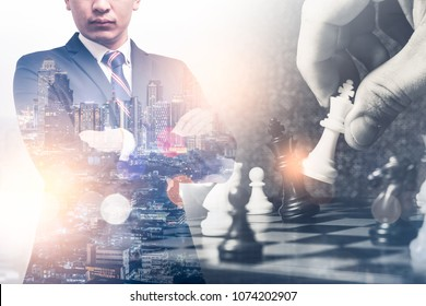 The double exposure image of the businessman standing during sunrise overlay with chess game image. the concept of strategy,intelligence and education.