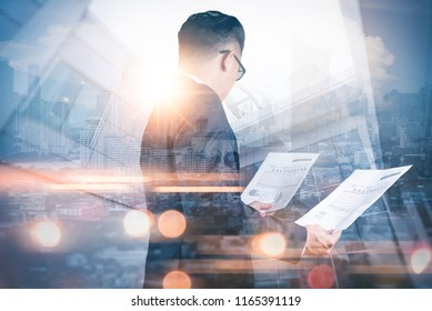 The double exposure image of the businessman standing and looking to documents during sunrise overlay with cityscape image. The concept of modern life, business, city life and internet of things.