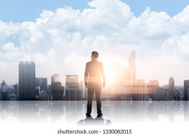The double exposure image of the businessman standing back on the rooftop during sunrise overlay with cityscape image. The concept of modern life, business, city life and internet of things.