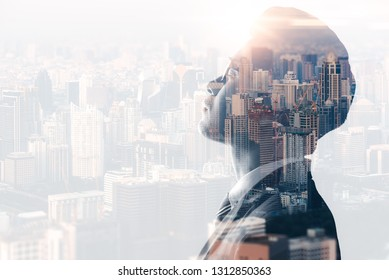 The double exposure image of the businessman thinking during sunrise overlay with cityscape image. The concept of modern life, business, city life and internet of things.