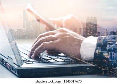 The double exposure image of the businessman using a laptop computer during sunrise overlay with cityscape image. The concept of modern life, business, programming and internet of things.