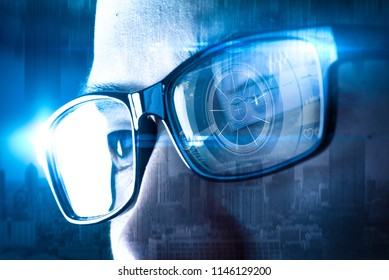 The double exposure image of the businessman wear a smart glasses overlay with cityscape image and futuristic hologram. The concept of modern life, technology, iris scanner and internet of things
