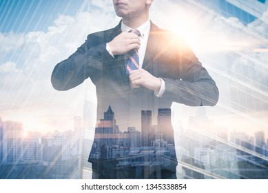 The double exposure image of the businessman wearing a necktie and suit during sunrise overlay with cityscape image. The concept of modern life, business, city life and internet of things.