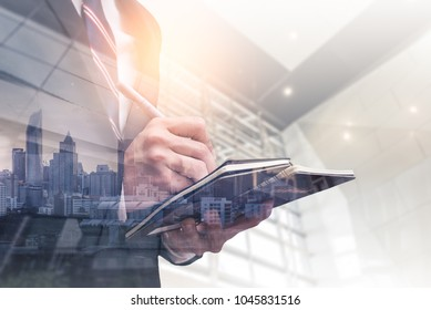 The double exposure image of the businessman writing on his notebook during sunrise overlay with cityscape image. The concept of management, business, city life and professional.
