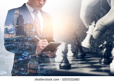 The double exposure image of the businessman writing on his notebook during sunrise overlay with chess game image.  the concept of strategy, victory, business, win, games, intelligence and education.