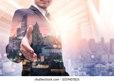 The double exposure image of the businessmanlift up the hand for handshake or deal during sunrise overlay with cityscape image. The concept of modern life, business, city life and partnership.