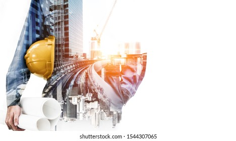 Double exposure image of construction worker holding safety helmet and construction drawing against the background of surreal construction site in the city.