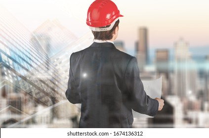 The double exposure image of the engineer standing back with a cityscape background