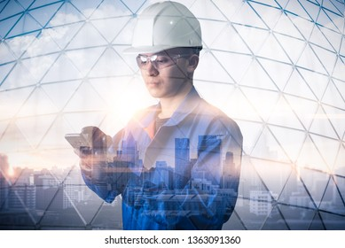The double exposure image of the engineer using a smartphone during sunrise overlay with cityscape image. The concept of engineering, construction, city life and future.