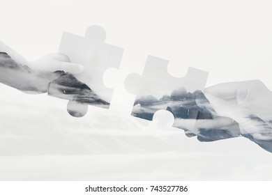 Double Exposure Image of Hands Connecting Puzzle Pieces Together