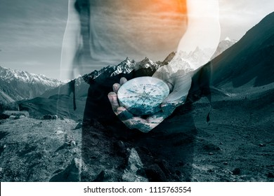 Double exposure image of snow mountain and male hands with hiking compass.