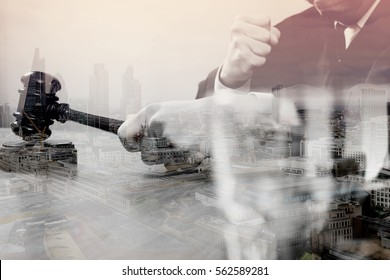 double exposure of justice and law concept.Male judge in a courtroom with the gavel,working with smart phone,digital tablet computer docking keyboard on wood table,London architecture city