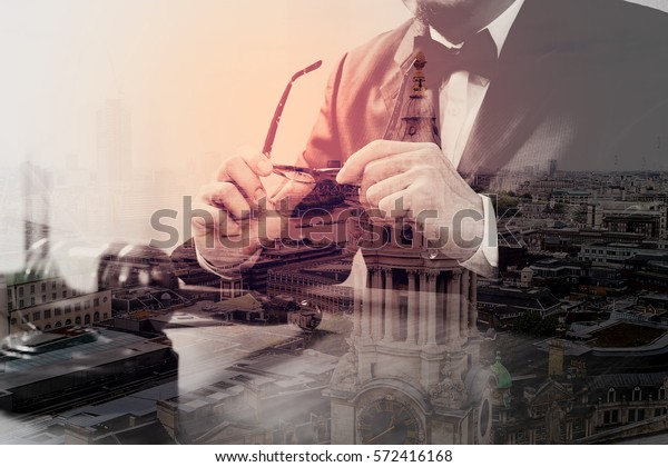 double exposure of justice and law concept.Male judge in a courtroom with the gavel,working with smart phone,digital tablet computer docking keyboard,eyeglasses,on wood table,London architecture city