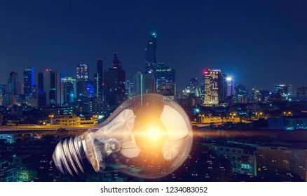 Double exposure of  Light bulb glowing and city night background.idea or energy concept.
