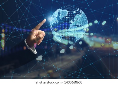 Double exposure of male hand with digital model of Earth and city at night