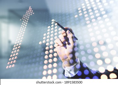 Double exposure of male hand with pen draws abstract virtual upward arrows hologram on blurred office background. Ambition and challenge concept