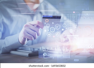 Double exposure of man hands holding a credit card and data theme drawing. E-commerce and technology concept.