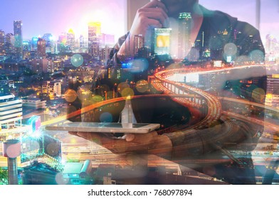 Double Exposure of Man or Male hold Digital Wireless Smart Tablet with Glowing Modern City Expressway or Highway at Night Twilight Represent Modern Business Communication or Real Estate Project Dev