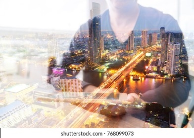Double Exposure of Man or Male hold Digital Wireless Smart Tablet with City Building Business Street and Bridge as High Speed Data Technology Networking and Real Estate ProJect Development