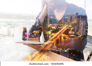 Double Exposure of Man or Male hold Digital Wireless Tablet with City Building Business Street and Bridge as High Speed Data Technology Innovation Networking and Real Estate ProJect Development Concep