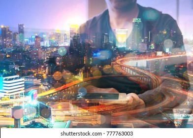 Double Exposure of Man or Male hold Digital Smart Tablet with Glowing Modern City Scenic, Expressway or Highway at Night or Twilight Represent Modern Business Communication or Real Estate Project Deve