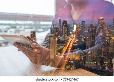 Double Exposure Of Man or Male use Digital Tablet Wireless thinking with Office building Glow at Night as Business Teamwork or Human Resources Strategy Concept.