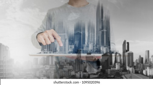 Double exposure, a man using digital tablet, and modern buildings hologram. Real estate business and building technology concept