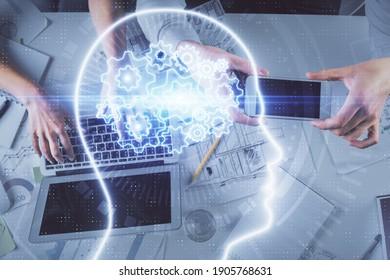 Doppelter Kontakt von Mann und Frau, die zusammen arbeiten und Hologramm-Zeichnung des menschlichen Gehirns. Brainstorm-Konzept. Computerhintergrund. Draufsicht.