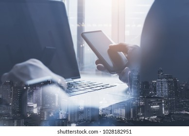 Double exposure man working on laptop computer using smart phone and smart city, internet application on phone and computer devices, startup business, software development, internet of things concept
