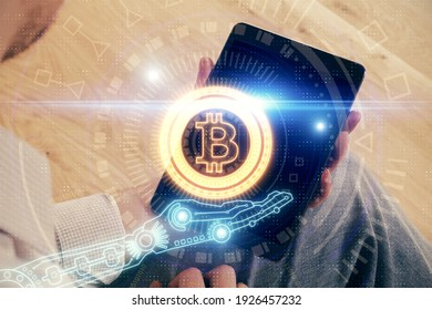 Double exposure of man's hands holding and using a phone and crypto currency blockchain theme drawing.