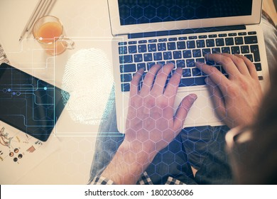 Double exposure of man's hands typing over computer keyboard and finger print hologram drawing. Top view. Personal security concept.