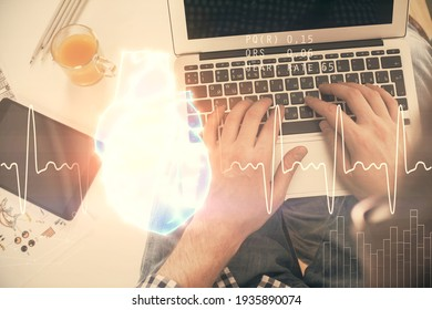 Double exposure of man's hands typing over computer keyboard and human heart hologram drawing. Top view. Medical education concept.