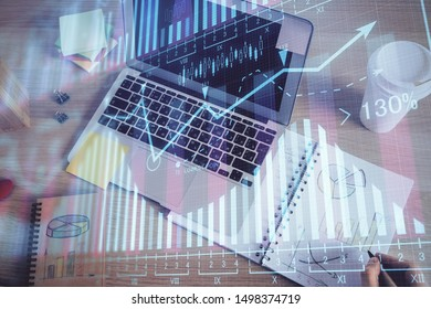 Double exposure of man's hands writing notes of stock market with forex chart.
