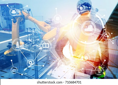 Double exposure of Manufacturing production industrial machine , factory robots arm in smart factory , engineer male stand with his back of machine with flare light effect. Blue tone.