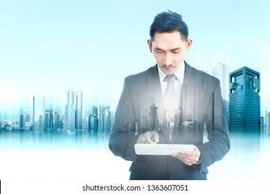 Double exposure of modern city and handsome asian businessman using digital tablet in his hand. Future technology concept