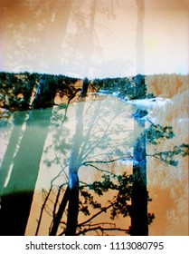 Double exposure natural landscape in distorted color. Vintage blurred analog photography with grain, dust and noise. Film photo in style lomography with chromatic aberration.