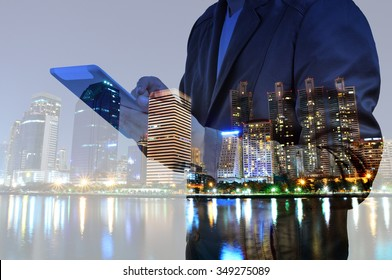 Double exposure of Night city and business man using digital tablet device as Business development concept.