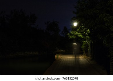 Double exposure night scene of person walking dark street illuminated with streetlights. The receding male silhouettes on the road in the park. Human figure in motion blur going along the city river