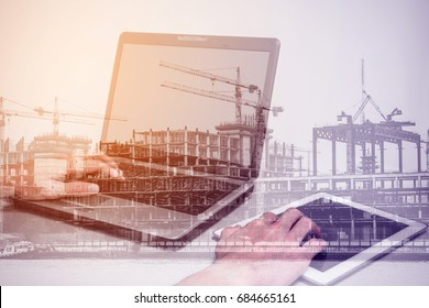Double exposure one using laptop computer and touch tablet pc and construction site representing modern engineering and technology concept.