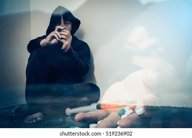 Double exposure overdose asian male drug addict.narcotic syringe on hand.