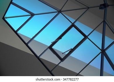 Double exposure photo of glazed aluminum structure and coffered ceiling with sky blue lighting. Sample of modern residential or office interior. Contemporary architectural motif.