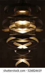 Double exposure photo of lighting fixture with ribbon-shaped structure. Realistic though unreal modern architecture / interior detail.