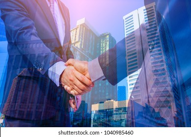 Double exposure photo.  Photo mix  building city and Shake hands. They are join hands  mean teamwork  and spirit beside  building background. Photo concept for business and team work.