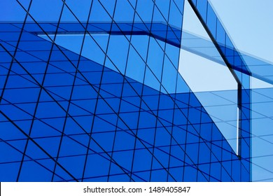 Double exposure photo of modern architecture fragment with glass wall, windows, ceiling or roof. Checkered transparent panels. Structural glazing. Abstract geometric background with blue grid pattern.