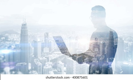 Double exposure photo stylish businessman wearing black shirt and glasses.Banker holding contemporary notebook hands,work online banking.Panoramic view modern skyscraper city background.Soft light