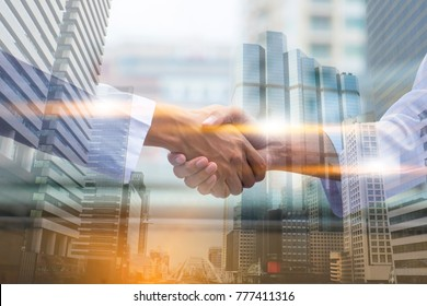 Double exposure picture.  Picture mix  building city and Shake hands. They are Shake hands mean teamwork  and spirit beside  building background. Photo concept for success   and team work.