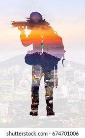 Double exposure portrait of photographer and city skyline.