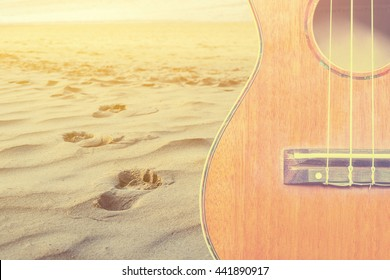 Double exposure portrait of a ukulele on the beach with footprints in the sand background,music concept